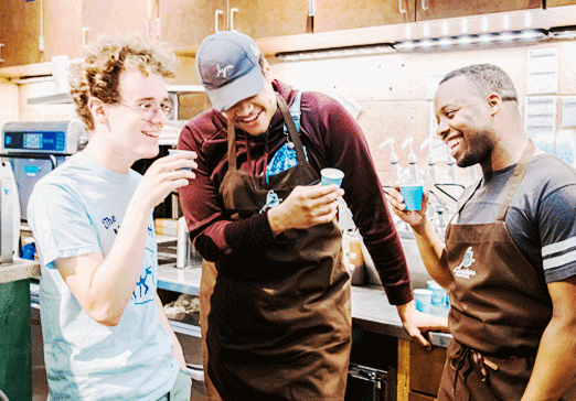 3 team members talking and drinking coffee