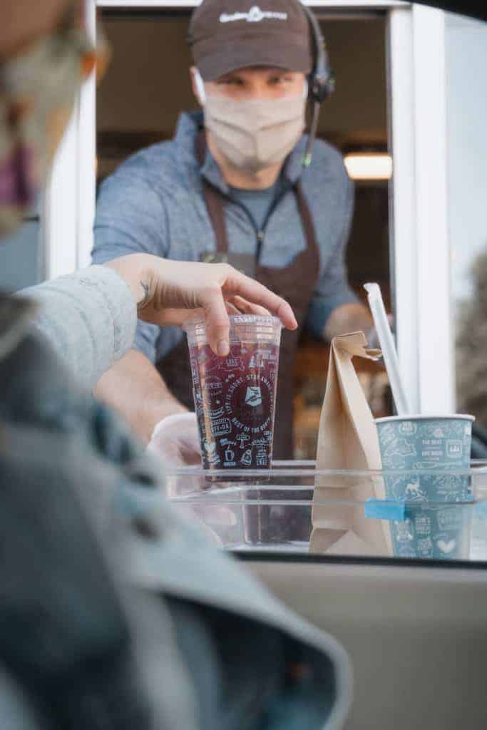 Barista handing drink out of drive-thru window wearing face covering and gloves.