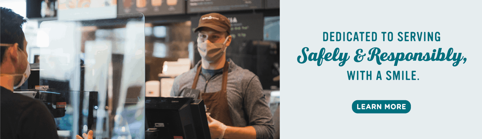 Caribou barista smiling behind plexi shield wearing face covering and gloves while customer orders