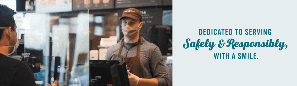 Barista standing behind plexi shield smile at guest while they order in store