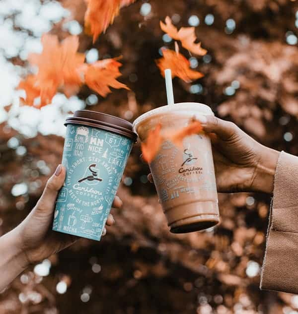 Caribou Coffee REAL pumpkin drinks held to the sky, cheersing