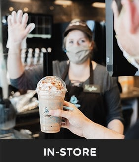 Barista wearing mask serving guests in-store