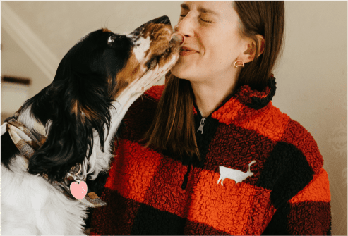 Woman wearing a Caribou Coffee fleece and a dog licking her face